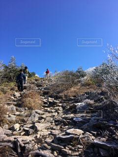 岩が多い丘の上に立っている人の写真・画像素材[1403949]