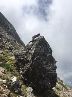 岩が多い丘の上に立っている人の写真・画像素材[1403957]