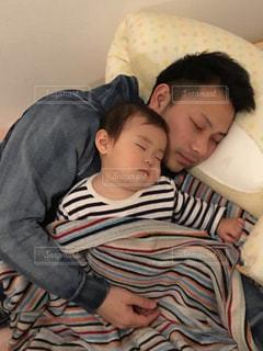 ベッドの上に横たわっている若い男の写真・画像素材[2204316]