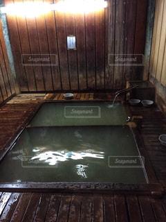 れんが造りの壁の隣に座っている木製のベンチの写真・画像素材[1020368]