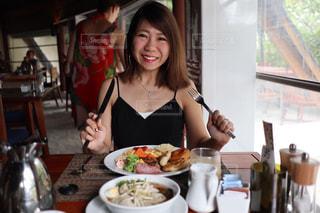 食品のプレートをテーブルに座っている女性の写真・画像素材[1659538]