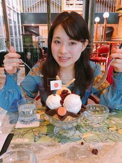食事のテーブルに座っている女性の写真・画像素材[931288]