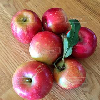 木製のテーブルの上に座って赤いリンゴの写真・画像素材[905330]