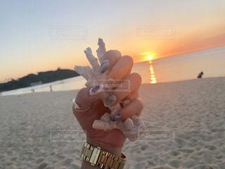 ビーチで水のボトルを持っている手の写真・画像素材[1351540]