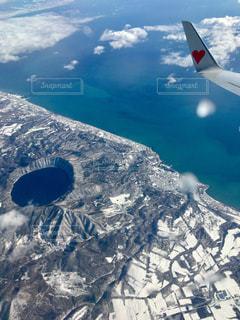 雪の覆われた山上空を飛ぶ飛行機 - No.907216