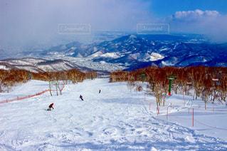 雪に覆われた山をスキーに乗っている人のグループの写真・画像素材[907973]