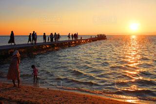 水の体の横に立っている人のグループ - No.908308