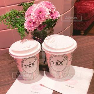 テーブルの上のピンクの花のミルクティーの写真・画像素材[937010]