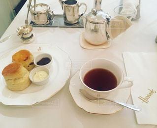 テーブルの上のコーヒー カップとプレートの写真・画像素材[948875]