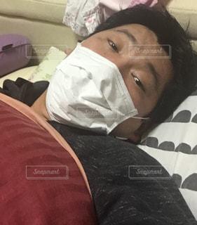 ベッドの上で横になっている人の写真・画像素材[1065766]