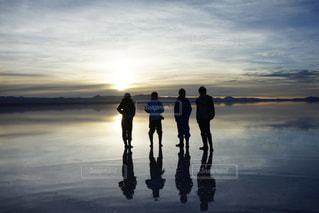 水の体の近くのビーチの上を歩く人々 のグループ - No.1040342