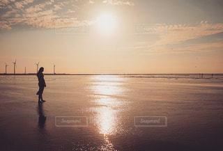 水の体の近くのビーチの上を歩く人々 のグループの写真・画像素材[1291778]