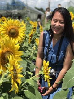 黄色の花の前に立っている女性の写真・画像素材[919455]