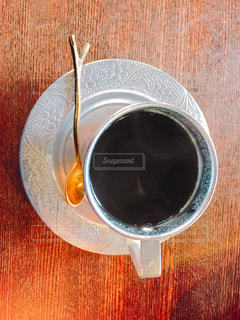 近くの木製のテーブルの上に座ってコーヒー カップの写真・画像素材[1450973]