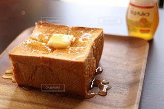 木製の皿の上に座っている厚切りトーストの写真・画像素材[1668277]