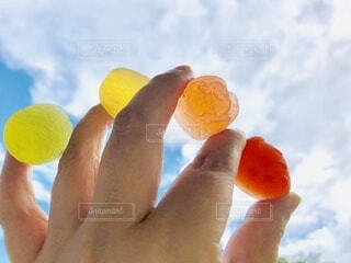 食べ物,空,屋外,カラフル,雲,手,オレンジ,手持ち,人物,人,たくさん,ポートレート,カラー,色,ゼリー,お気に入り,ライフスタイル,手元,色々