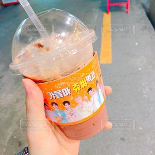 プラスチック製のカップを持っている手の写真・画像素材[927428]