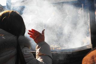 常香炉の煙を頭に浴びている女性の写真・画像素材[987250]