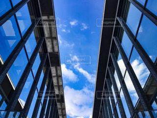 空が映り込むガラス張りの建物の写真・画像素材[1221627]