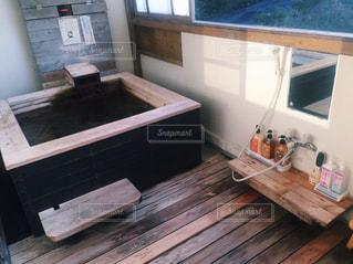 ウィンドウの横に座っている木製のベンチの写真・画像素材[998053]