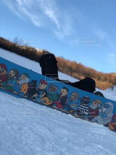 雪のスロープを下るスノーボードに乗っている間空気を通って飛んで男の写真・画像素材[947705]