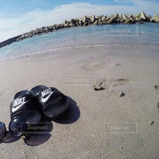 水の体の近くのビーチに、動物のぬいぐるみの写真・画像素材[927842]