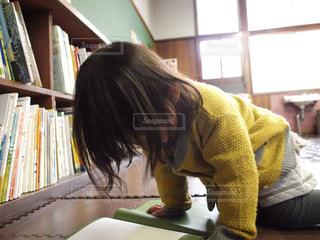 本の棚の前に座っている女性の写真・画像素材[737493]