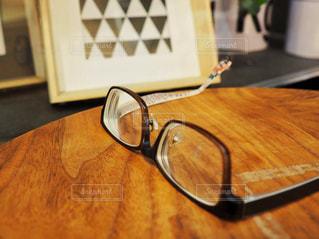 木製テーブルと眼鏡の写真・画像素材[1354928]