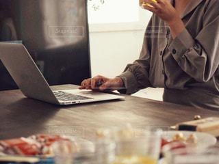 ラップトップを使用してテーブルに座っている人の写真・画像素材[1558221]
