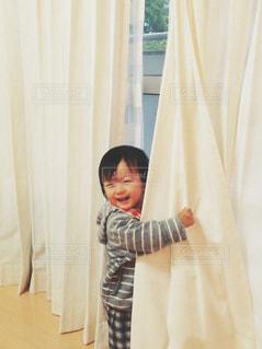 カーテンの前に立っている人の写真・画像素材[1629616]