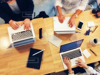 ラップトップを使ってテーブルに座っている人々のグループの写真・画像素材[2443229]