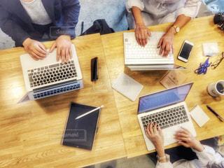 ノートパソコンを持ってテーブルに座っている人々のグループの写真・画像素材[2443435]