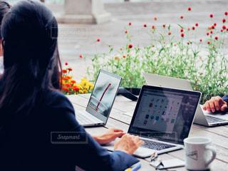 ノートパソコンを使ってテーブルに座っている人の写真・画像素材[2444092]