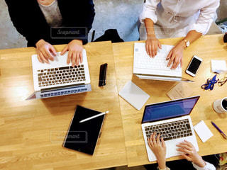 ノートパソコンを持ってテーブルに座っている人々のグループの写真・画像素材[2444190]