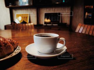 木製のテーブルの上に座っているコーヒーのカップの写真・画像素材[2915196]