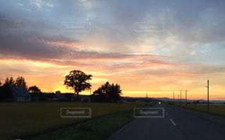 背景の夕日と道路の写真・画像素材[986177]