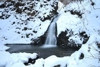 滝の隣に雪の山の写真・画像素材[936969]