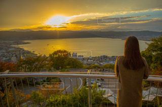 諏訪湖の夕日を眺める女性の写真・画像素材[933510]