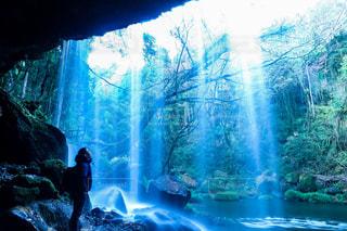 滝の隣に立っている人の写真・画像素材[934917]