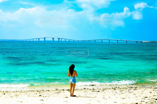 海の隣のビーチを横切って歩く人の写真・画像素材[2352470]