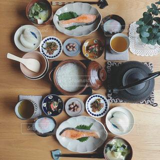 食品のプレートをテーブルに座っている人々 のグループの写真・画像素材[1488325]