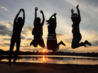 夕日の前でジャンプの写真・画像素材[4322162]