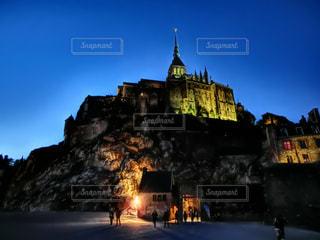 バック グラウンドでモン ・ サン ・ ミシェルと夜ライトアップ城の写真・画像素材[1683371]