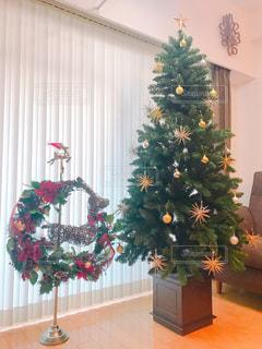 クリスマス ツリーの横にある花の花瓶や家具でいっぱいの部屋の写真・画像素材[938983]