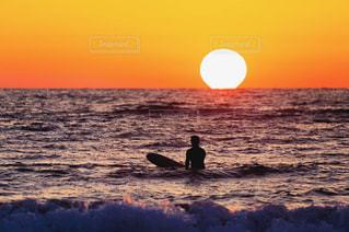 水の体の上に日没の前に立っての写真・画像素材[957538]