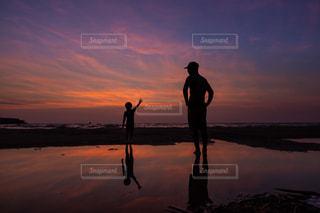 夕日の前に立っている男の写真・画像素材[2140478]