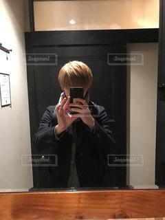 カメラにポーズ鏡の前に立っている人の写真・画像素材[1699996]