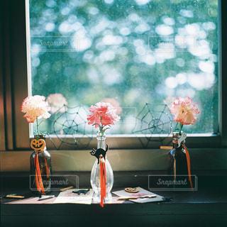 ウィンドウの横にあるテーブルの上の花の花瓶の写真・画像素材[1233732]