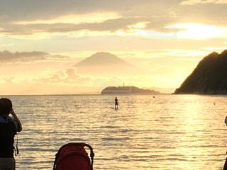 水の体の上に日没の前に立っている人の写真・画像素材[962883]
