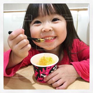 コーヒーのカップをテーブルに座っている少女の写真・画像素材[1603433]